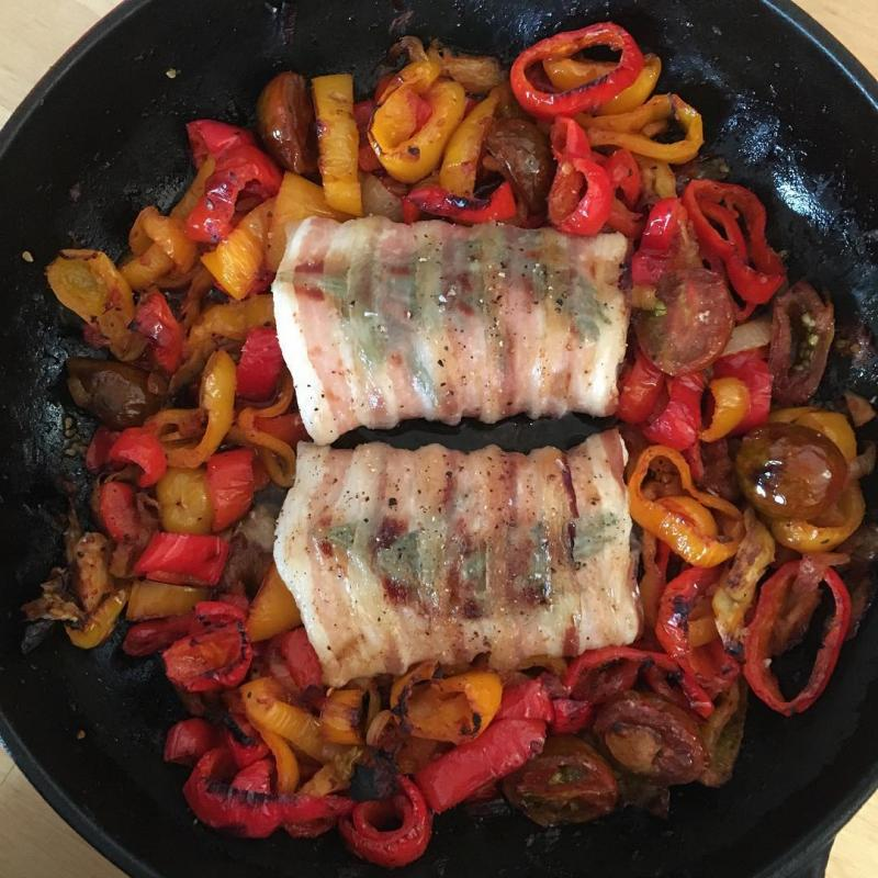 Pancetta-wrapped cod with peppers and tomatoes.