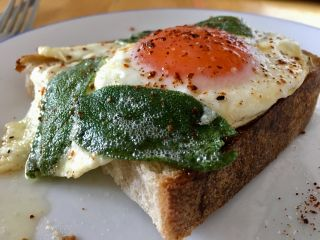 Eating a piece of toast with an egg and fried sage leaves on top. 🍳