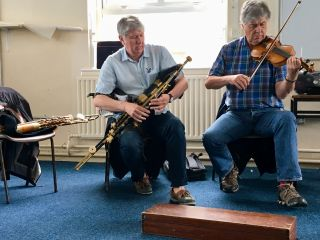 Pádraic Mac Mathúna playing Seamus Ennis's pipes and Paddy Glackin playing Seamus Ennis's fiddle.