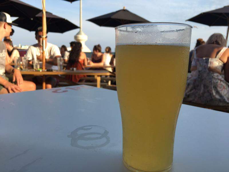 Checked in at Shelter Hall Raw. Having a beer on the beach — with Jessica