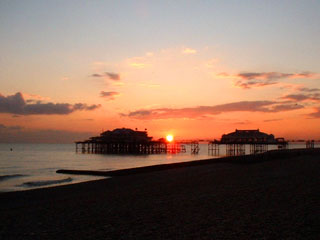 Brighton's West Pier illuminated by a red sunset
