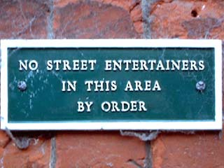 A sign that reads NO STREET ENTERTAINERS IN THIS AREA BY ORDER