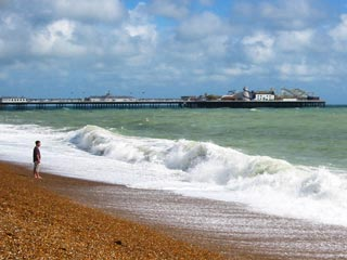 waves crashing on the beach with the palace pier in the background