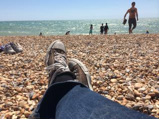 On Brighton beach in the sunshine, watching the tide come in. The waves are surprisingly big today.