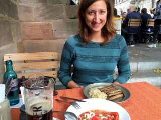 Jessica is pleased with her plate of sausages and sauerkraut.