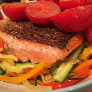 Salmon and tomatoes on vegetables julienne.